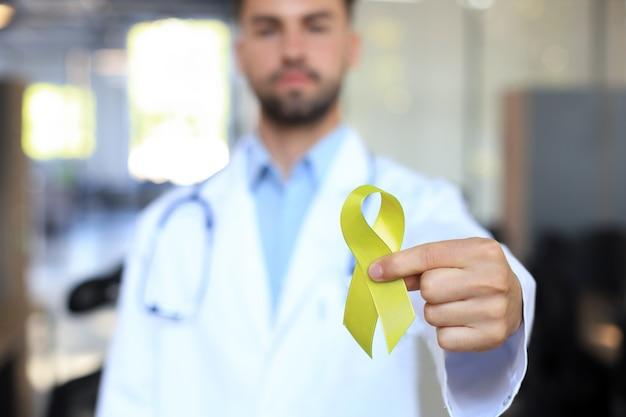 Mão do médico com fita de ouro amarelo, conscientização do sarcoma, conscientização do câncer infantil, dia mundial da prevenção do suicídio.