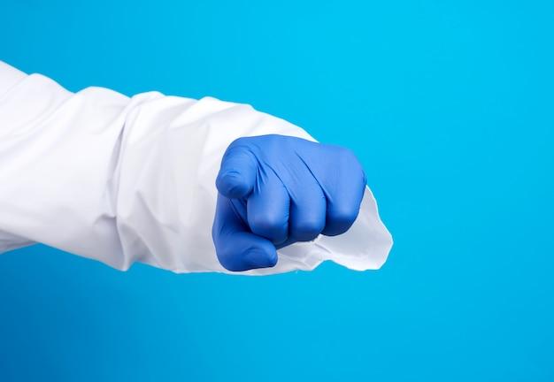 Mão do médico em luva de látex azul e jaleco branco, o indicador se estende para a frente