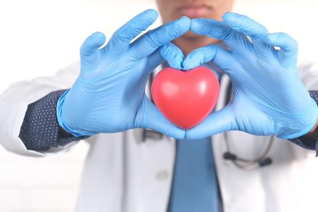 Mão do médico em luvas de proteção segurando um coração vermelho sobre azul