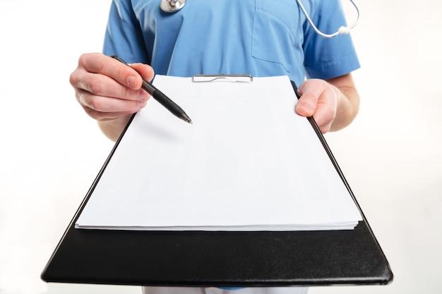 Mão do médico masculino segurando uma caneta e uma prancheta com papel em branco e estetoscópio isolado na parede branca