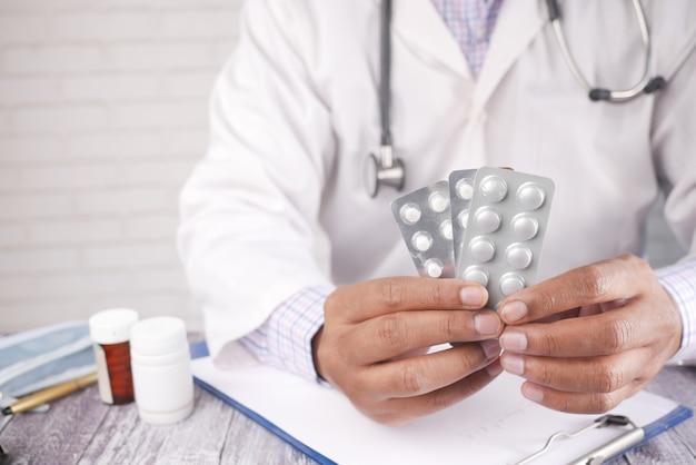 Mão do médico segurando o blister na mesa da clínica