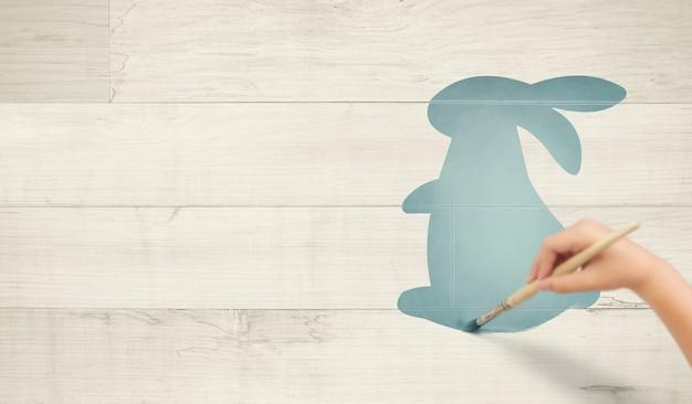Mão do menino pintando o coelho da páscoa em madeira branca
