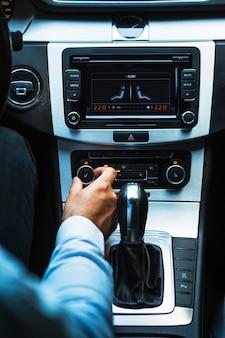 Mão do motorista, ajustando o botão de áudio no carro