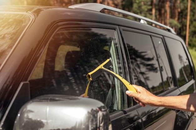Mão do motorista com limpador de carro, limpando e lavando vidros automotivos no verão