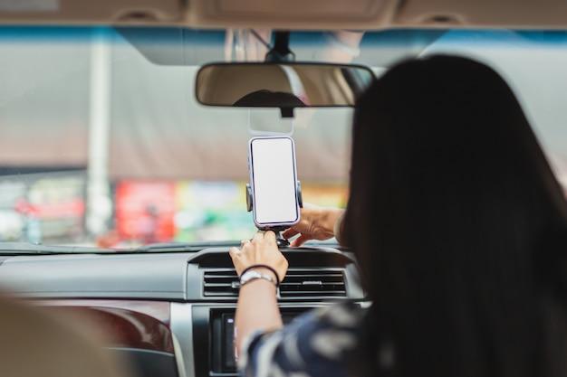 Mão do motorista da mulher ajustar o telefone celular para a direção.
