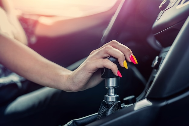 Mão do motorista feminino mudando a maçaneta de mudança manualmente antes do início do passeio
