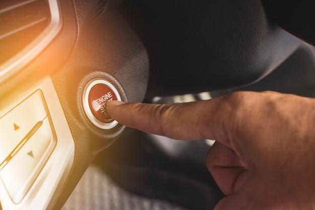 Mão do motorista pressionando o botão de partida / parada do motor para ignição do motor em um carro de luxo.