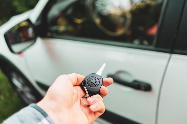Mão do motorista segurando as teclas do controle remoto sem fio para abrir o carro
