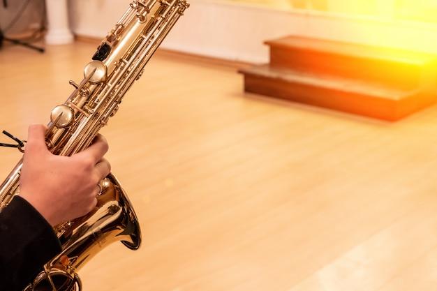 Mão do músico tocando saxofone jazz durante performance ao vivo no palco