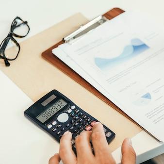 Mão do negócio que estuda o conceito do relatório do gráfico