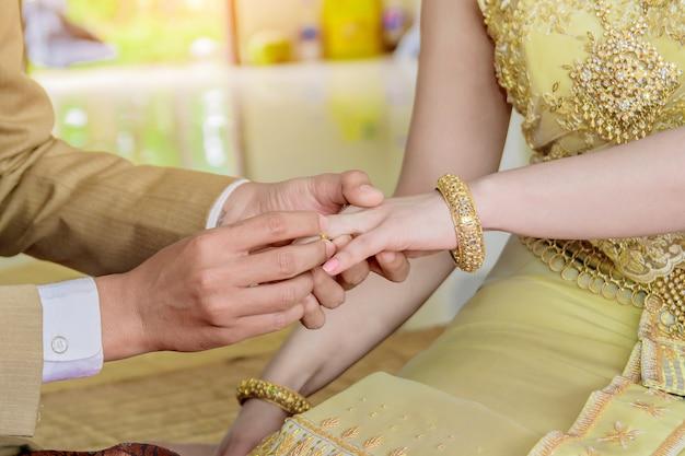 Mão do noivo colocando uma aliança no dedo da noiva.
