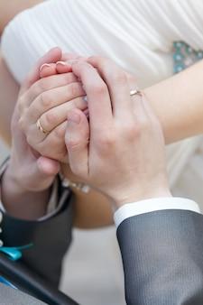 Mão do noivo e da noiva com alianças em uma festa de casamento