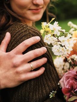Mão do noivo no ombro da noiva, a noiva segurando o buquê sorri