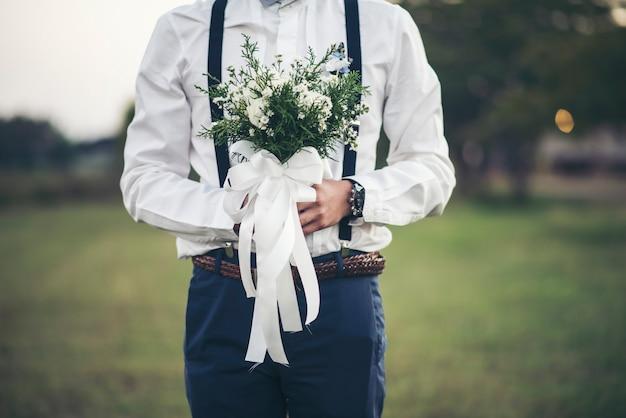 Mão do noivo segurando flor de amor no dia do casamento