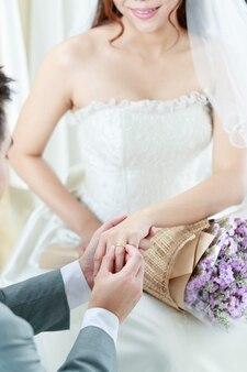 Mão do noivo usa uma aliança de casamento para a noiva.