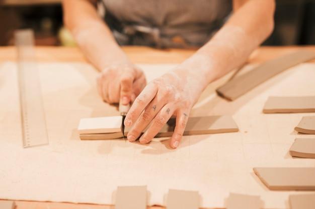Mão do oleiro feminino cortando a argila em forma de telha com ferramenta na mesa de madeira