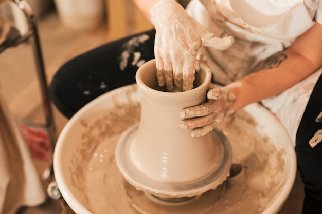 Mão do oleiro feminino fazendo pote de cerâmica com barro na roda de oleiro