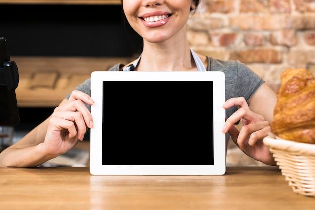 Mão do padeiro feminino mostrando a tabuleta digital de tela em branco na mesa