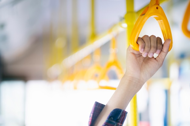 Mão do passageiro do close up que guarda o punho no transporte público.