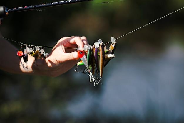 Mão do pescador escolhendo isca na linha de pesca