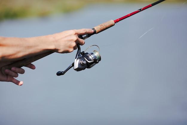 Mão do pescador pesca no fundo desfocado