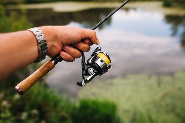 Mão do pescador segurando a vara de pescar ao ar livre