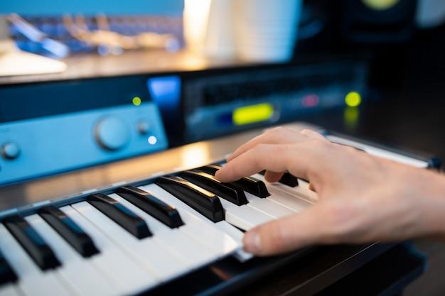 Mão do pianista pressionando uma das teclas do teclado do piano enquanto grava música em um estúdio contemporâneo