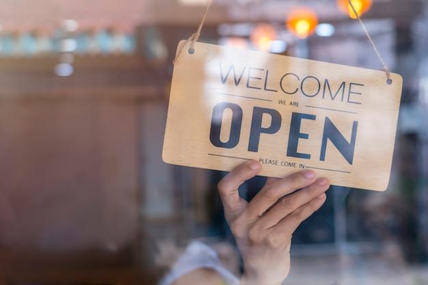 Mão do proprietário asiático de varejo, mulher de café girando a placa de sinalização para abrir.