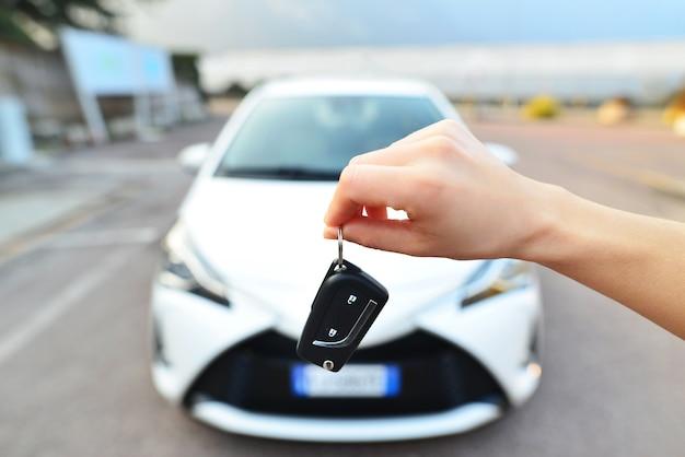 Mão do proprietário segurando a chave de entrega para os compradores
