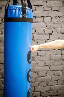 Mão do pugilista e saco de pancadas azul no ginásio.
