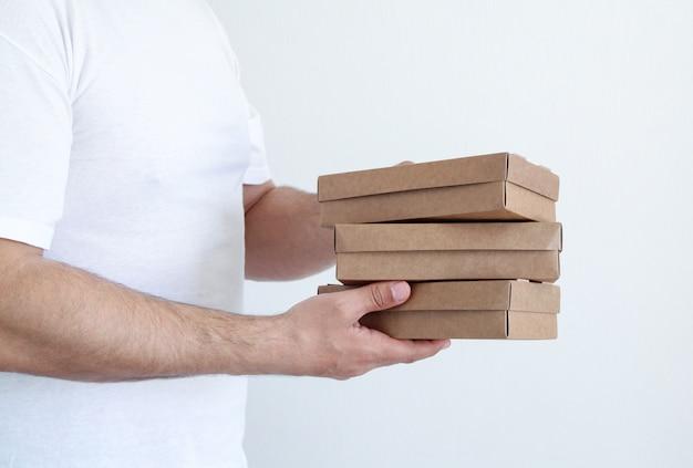 Mão do `s do homem novo do correio com as caixas da caixa do pacote dentro de casa no fundo branco