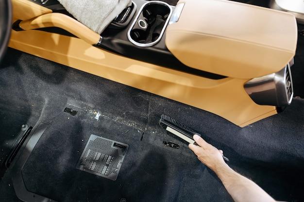 Mão do trabalhador com escova limpa o interior do carro, lavagem a seco e detalhamento.