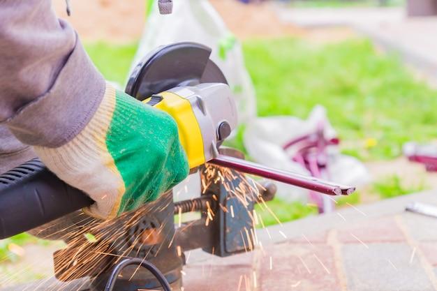 Mão do trabalhador cortando metal com moedor. faíscas ao moer ferro
