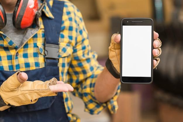 Mão do trabalhador manual, mostrando smartphone com tela branca