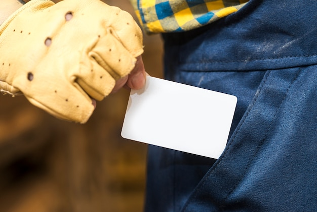 Mão do trabalhador manual, tirando o cartão de visita branco do bolso