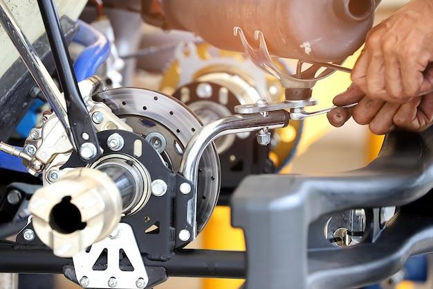 Mão do trabalhador que aperta ou que afrouxa uma porca de um parafuso com uma chave para a peça dos automotives.