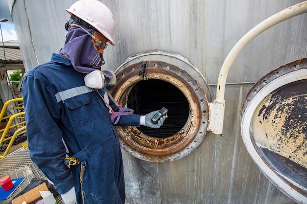 Mão do trabalhador segurando detector de gás, inspeção e teste de segurança de gás no tanque de aço inoxidável frontal para trabalhar dentro de confinamento
