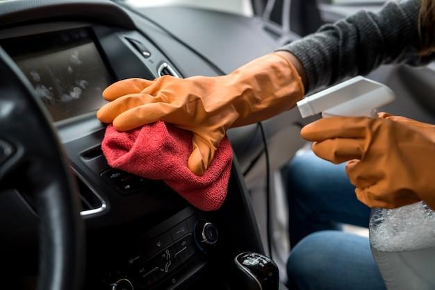 Mão do trabalhador usa luva de limpeza do interior do carro para prevenção covid-19