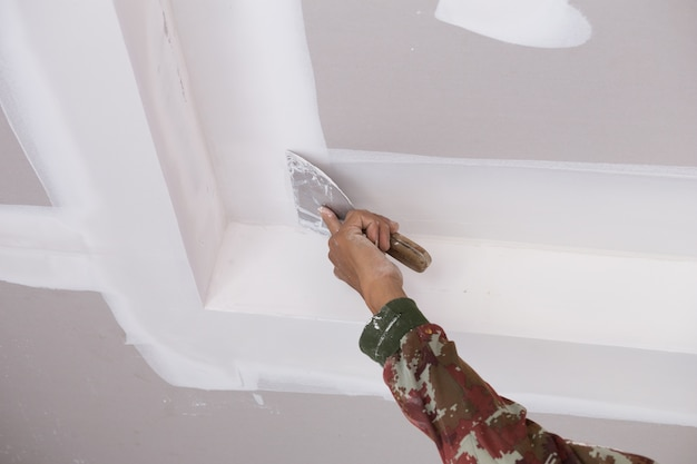 Mão do trabalhador usando juntas de teto de gesso gesso