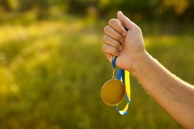 Mão do vencedor segurando medalha de ouro com fita