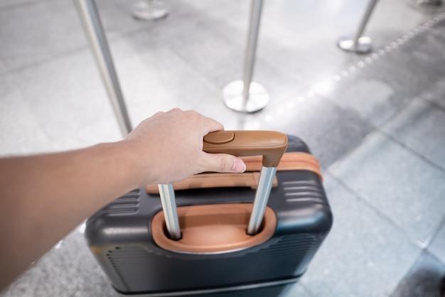 Mão do viajante que guarda a mala de viagem em um aeroporto.