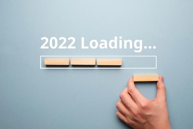 Mão dobras do conceito de blocos de madeira de carregamento de ano novo 2022.
