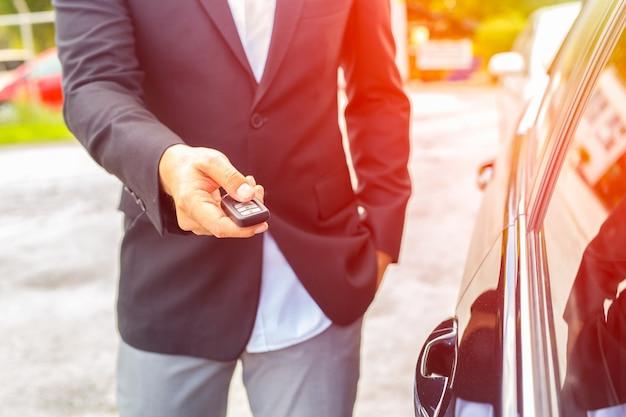 Mão dos homens pressiona os sistemas de alarme de carro de controle remoto