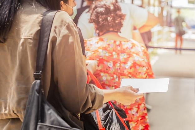 Mão dos passageiros segurando o cartão de embarque na fila para a partida. Foto Premium