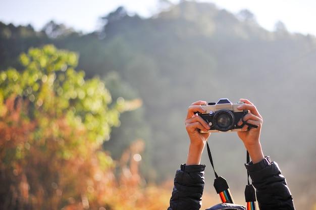 Mão e câmera do fotógrafo na floresta. seu amor pela fotografia e sua câmera.