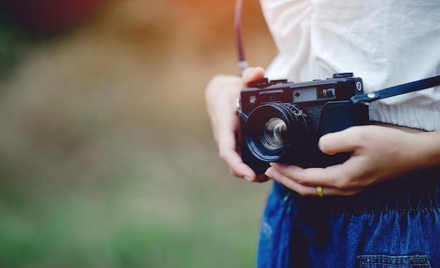 Mão e câmera do fotógrafo segurando e carregando a câmera para tirar fotos