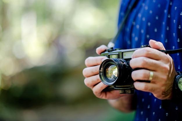 Mão e câmera do fotógrafo