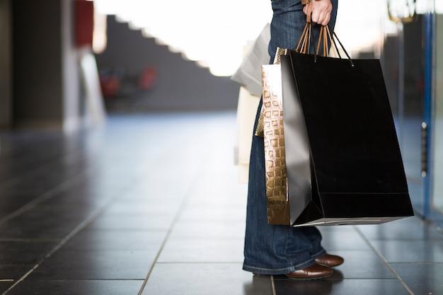 Mão e pernas com sacolas de compras