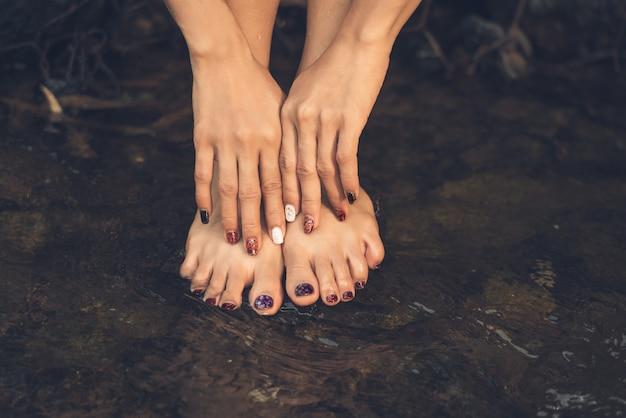 Mão e pés femininos dedo arte pintar unhas na água