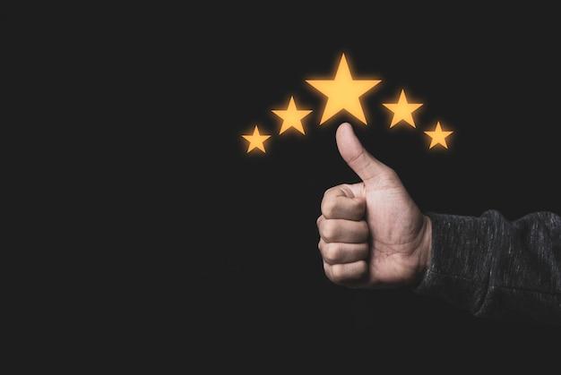 Mão e polegar levantam-se com cinco estrelas amarelas sobre fundo preto, melhor satisfação do cliente e avaliação de produto e serviço de boa qualidade.